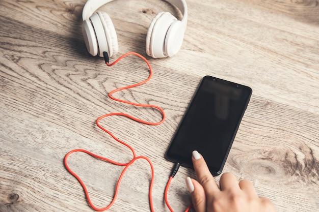 Mulher segurando o telefone e o fone de ouvido na mesa