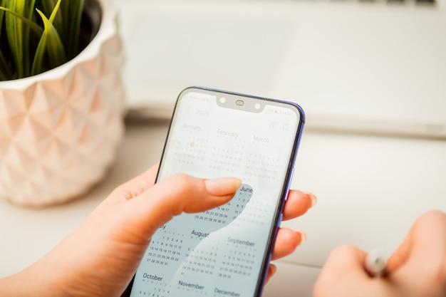 Mulher segurando o telefone e usando o calendário