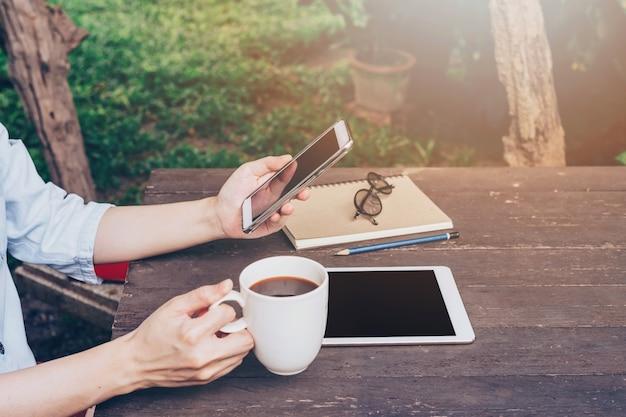 Mulher segurando o telefone e usando o telefone na mesa no jardim na cafeteria com tonificado vintage.