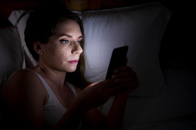 Mulher segurando o telefone enquanto está na cama