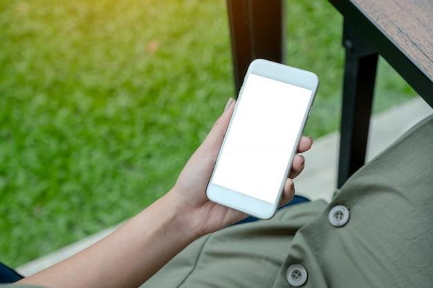 Mulher segurando o telefone inteligente branco com tela em branco