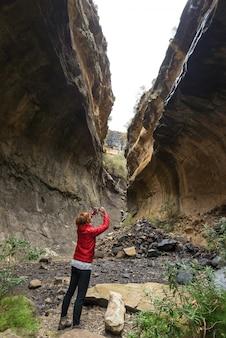 Mulher segurando o telefone inteligente e tirando foto no penhasco dentro do canyon na luz de fundo