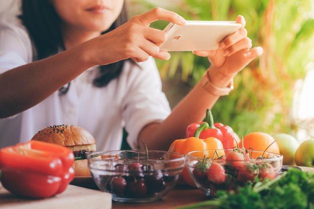Mulher segurando o telefone inteligente tirar uma foto de comida na mesa.