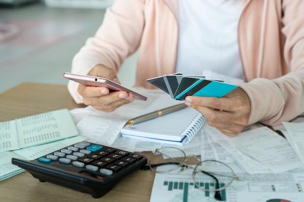 Mulher segurando o telefone móvel e cartões de crédito, conta e salvando o conceito.