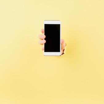 Mulher segurando o telefone no buraco embrulhado em fundo rosa