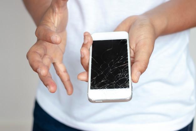 Mulher segurando o telefone que caiu a tela, rachada na mão, muito triste.