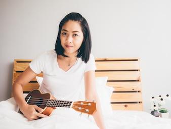 Mulher segurando o ukulele em seu quarto aconchegante.