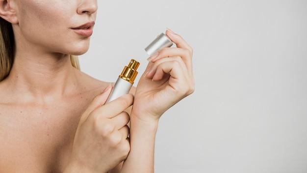 Mulher segurando o vaporizador de perfume