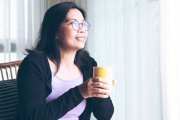 Mulher segurando óculos segurando uma caneca amarela de café sentada na sala de estar em casa
