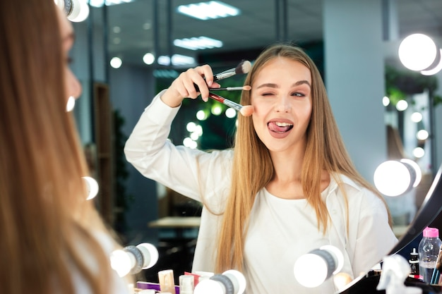 Mulher segurando os pincéis de maquiagem fazendo careta