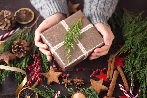 Mulher segurando os presentes de natal colocados sobre uma mesa de madeira.
