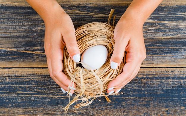 Mulher segurando ovo no ninho de palha