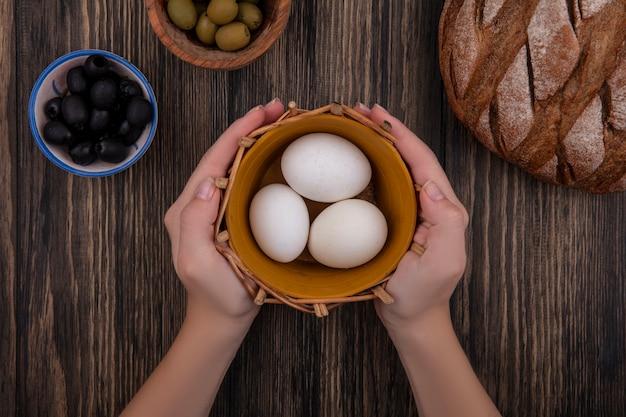 Mulher segurando ovos de galinha na cesta com azeitonas e pão preto em fundo de madeira.
