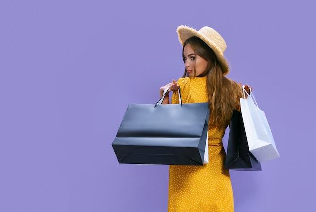 Mulher segurando pacotes depois de fazer compras no fundo roxo com desconto em vendas de sexta-feira negra