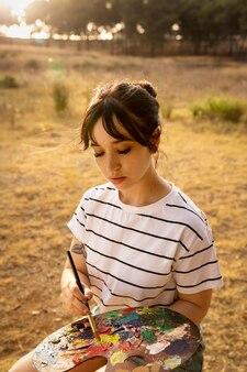 Mulher segurando paleta de tinta com pincel