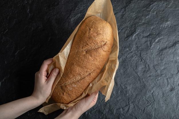 Mulher segurando pão fresco embrulhado.