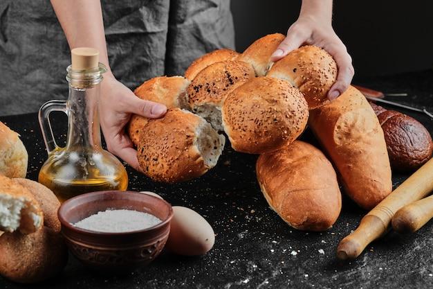 Mulher segurando pão na mesa escura com ovos, tigela de farinha e copo de óleo.