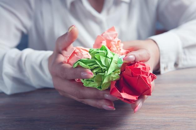 Mulher segurando papéis amassados nas mãos