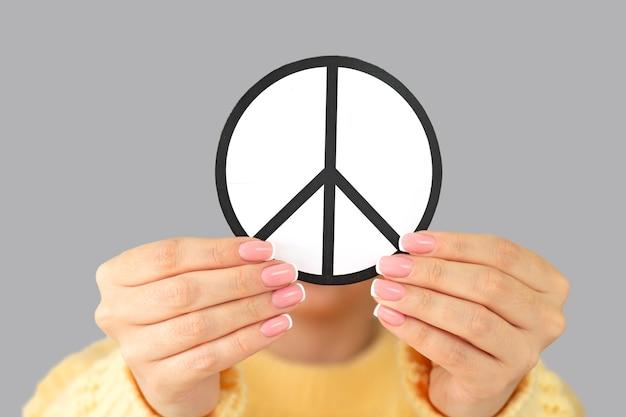 Mulher segurando papel símbolo de paz close-up. conceito de liberdade, amor e paz