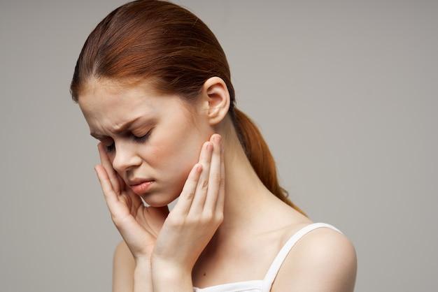 Mulher segurando para sentir dor no rosto durante tratamento de estúdio de dentes