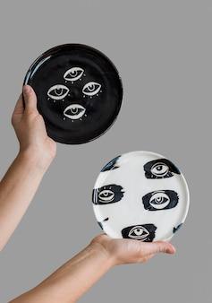 Mulher segurando peças de cerâmica feitas por ela mesma