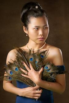 Mulher segurando penas de pavão