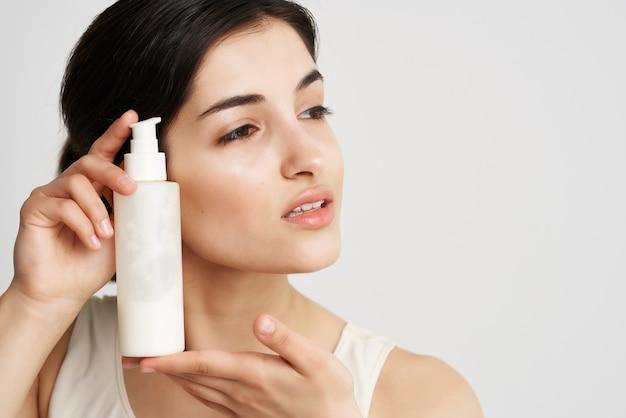 Mulher segurando perto de pele limpa com loção facial