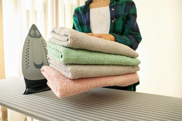 Mulher segurando pilha de toalhas na tábua de passar com ferro