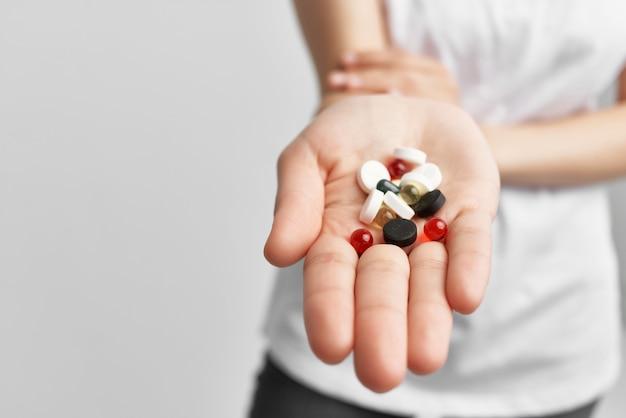 Mulher segurando pílulas multicoloridas em um medicamento de farmácia