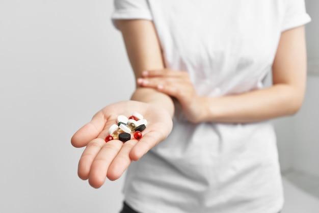 Mulher segurando pílulas multicoloridas em um remédio de farmácia de palma