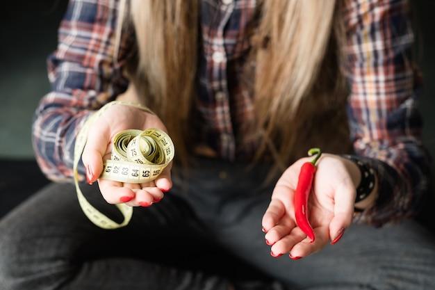 Mulher segurando pimenta fresca com fita métrica torcida na mão.