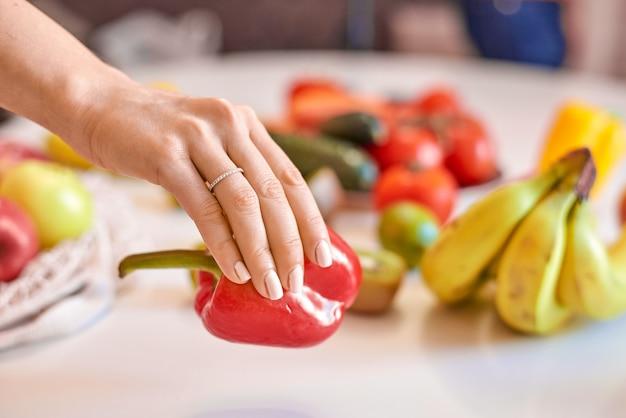 Mulher segurando pimenta vermelha com outras frutas