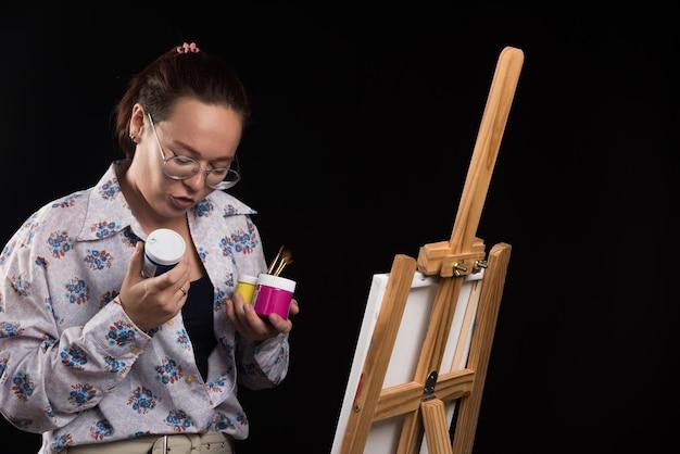 Mulher segurando pincel e pinta de preto