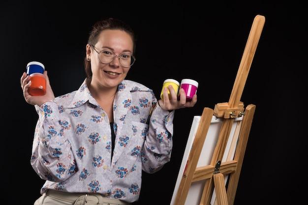 Mulher segurando pincel e tintas em fundo preto