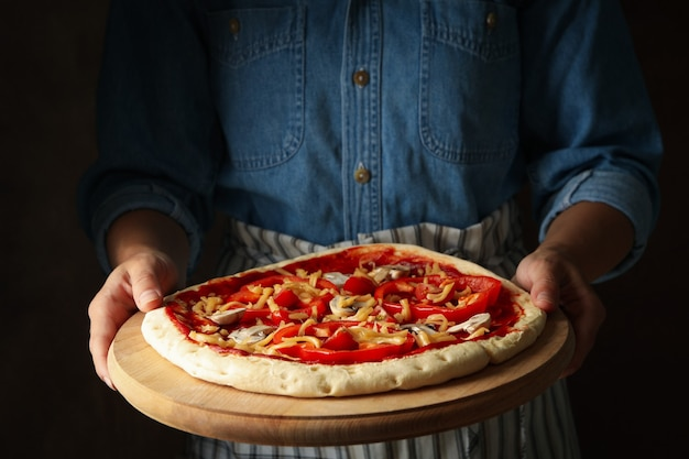 Mulher segurando pizza crua