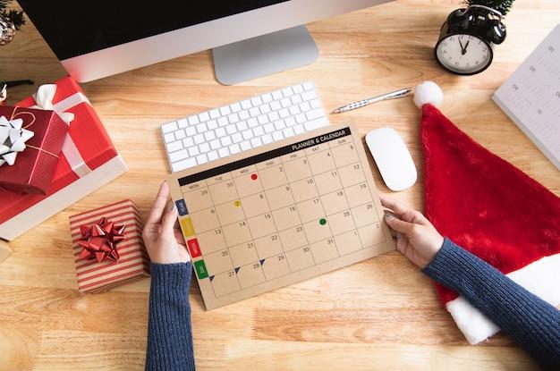 Mulher, segurando, planejador calendário, em, feriado natal, em, escritório, com, decoração natal