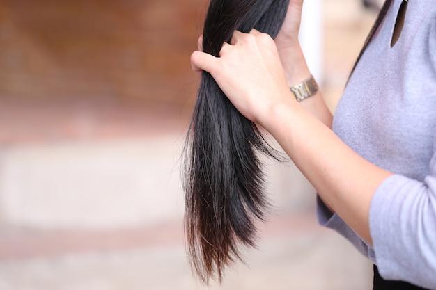 Mulher segurando pontas de cabelo danificadas