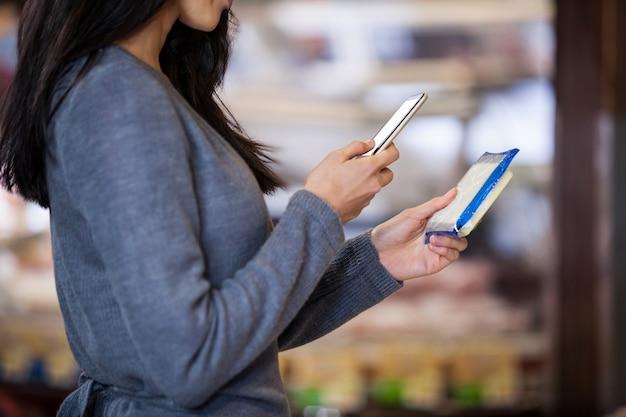 Mulher segurando produtos lácteos e usando telefone celular