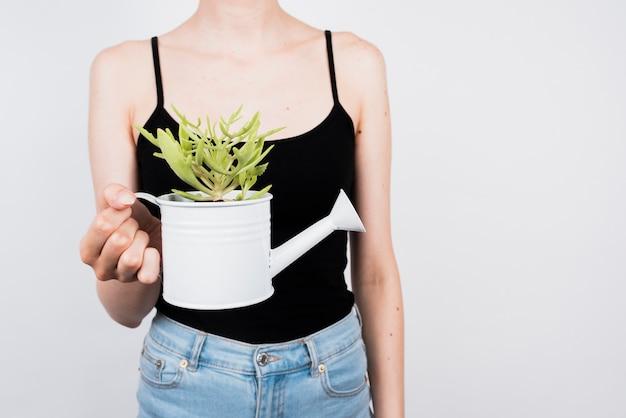 Mulher segurando regador com planta