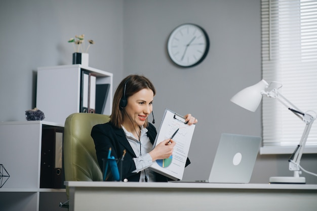Mulher segurando relatório financeiro de papel conversa na webcam, faça videochamada no escritório, treinador de negócios, olhando para a câmera, fale as estatísticas do programa, explique a estratégia de marketing para o cliente