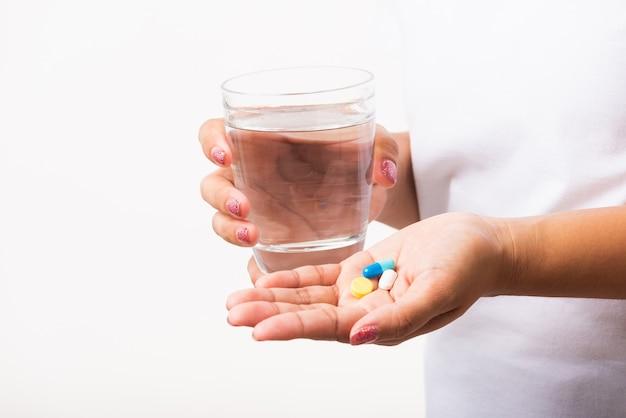 Mulher segurando remédios com um copo d'água