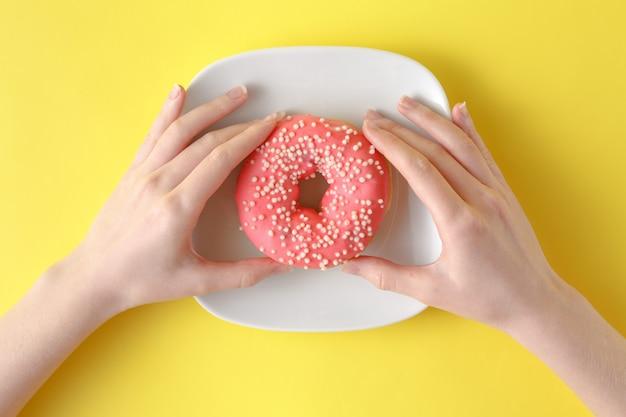 Mulher segurando rosquinha deliciosa na cor de fundo