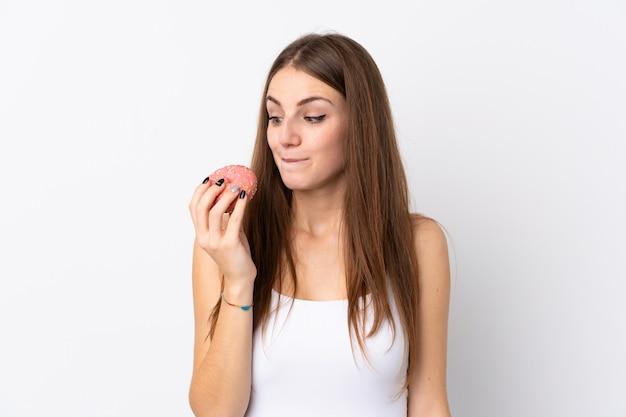 Mulher segurando rosquinhas sobre parede branca
