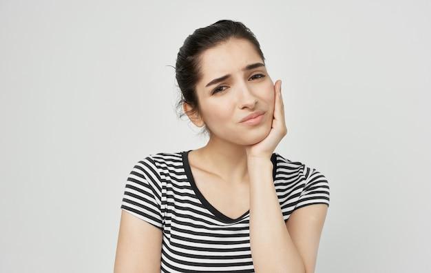 Mulher segurando rosto, problemas de saúde, dentes, remédio para dor