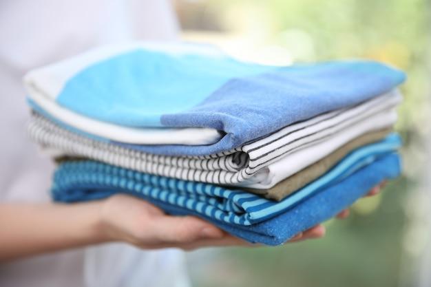 Mulher segurando roupas dobradas nas mãos, closeup