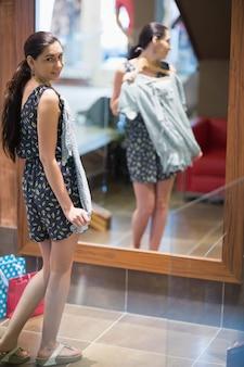 Mulher segurando roupas e olhando no espelho