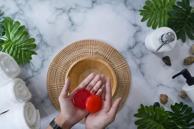 Mulher segurando sabonetes orgânicos sobre fundo de mármore.