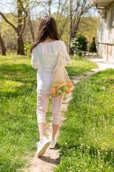 Mulher segurando saco reutilizável andando lá fora