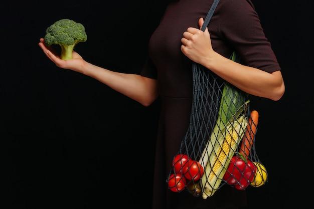 Mulher segurando sacola de barbante reutilizável cheia de vegetais frescos sobre preto