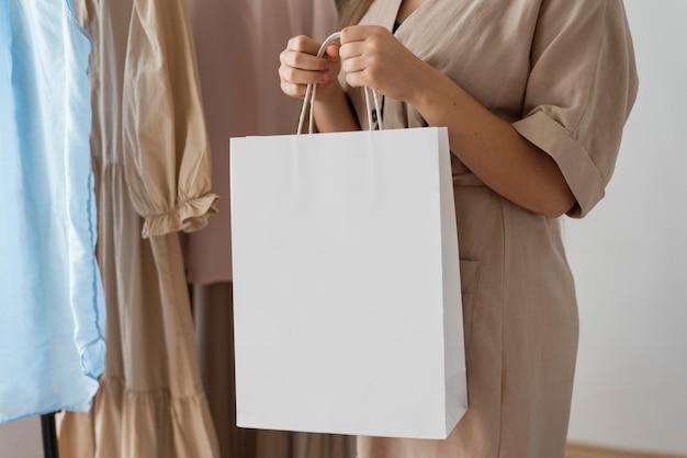 Mulher segurando sacola de compras com roupas